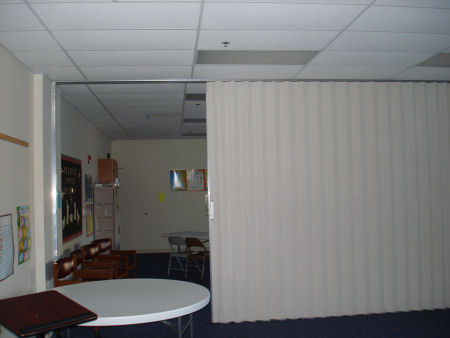 A view with the movable wall mostly closed in this commercial fit-up added by Anthony and Company Construction