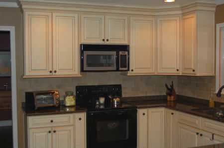 This view shows off the cabinetry, the microwave and the cooking area of the new kitchen, built by Raleigh Interiors Contractor Anthony and Company Construction