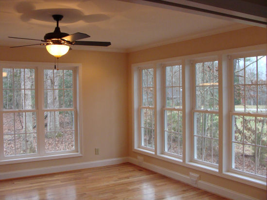 A shot showing a corner view out the sunroom windows, along with the central fan/light, built by Raleigh Sunroom Contractor Anthony and Company Construction